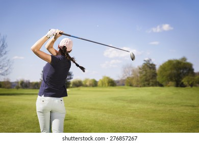 Female golf player swinging golf club.