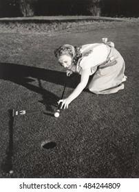 Female golfer crouching to line up a shot