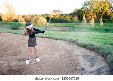 A Female Golfer Escaping a Bunker Shot. A shot of a young girl hitting the ball out of the bunker during a round of golf.