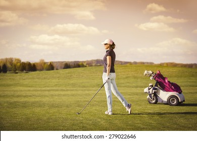 Female golfer on fairway with golf club and bag with empty copyspace.