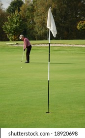 Female golfer putting on the green