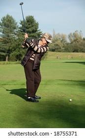 Female golfer tees off