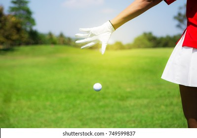 Female golfers holding a golf ball / selective focus