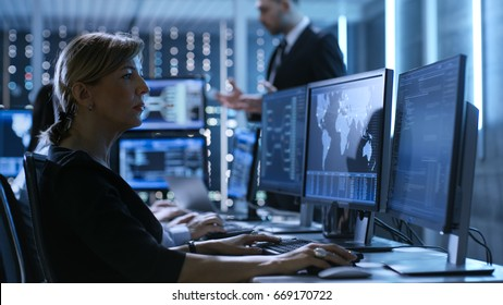 Female Government Employee Works in a Monitoring Room. In The Background Supervisor Holds Briefing. Possibly Government Agency Conducts Investigation.