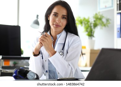 Female GP sitting at worktable in office looking in camera portrait