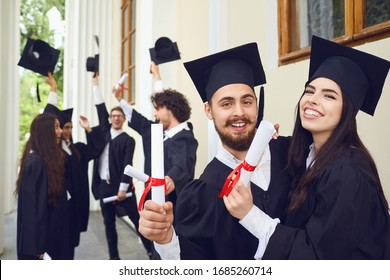 Female graduates with diplomas in their hands hugging