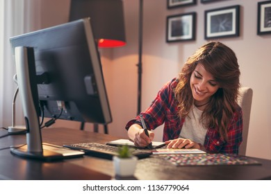 Female graphic designer working in a home office, choosing a color from a color palette