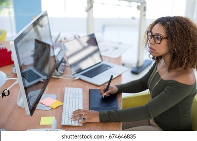 Female graphic designer working on computer while using graphic tablet at desk in the office