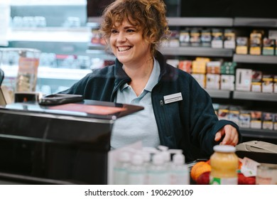Female grocery store manager working at checkout counter. Woman cashier working at supermarket checkout.