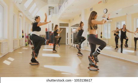 Female group of kangoo jumping in gym