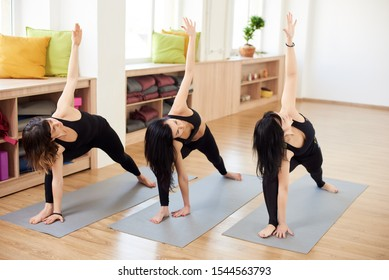 Female group of three experienced yogi practicing together in Extended side angle pose. Exercising with inclining, stretching and lifting hand up. Yoga classes in gym. Fitness and people concept