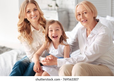 Female guardianship. Delighted positive nice family sitting together and having fun while having a wonderful time at home