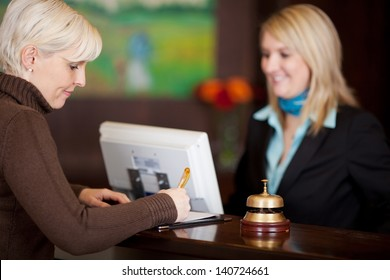 female guest filling up a formular at hotel counter