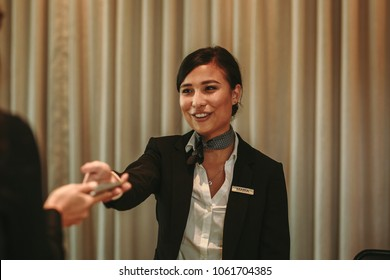 Female guest paying with mobile phone in hotel at the reception during check-out. Female receptionist receiving payment for hotel room from client in hotel.