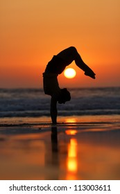 female gymnast doing a handstand in sunset at beach