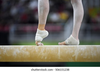 Female gymnast on balance beam during competition