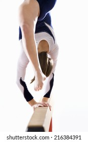 Female gymnast performing on balance beam