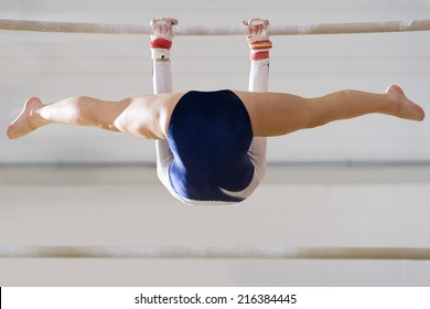 Female gymnast performing on bar, low angle view