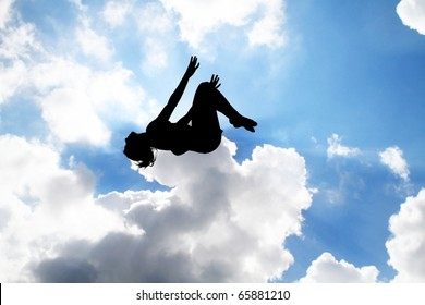 female gymnast silhouette jumping on trampoline in sky
