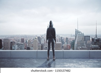 Female hacker with hood standing on rooftop with city view. Hacking and network concept