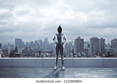 Female hacker with hood standing on rooftop with city view. Hacking and criminal concept