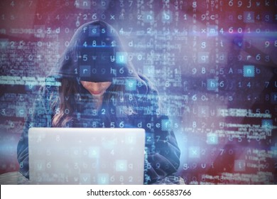 Female hacker using laptop against abstract black room