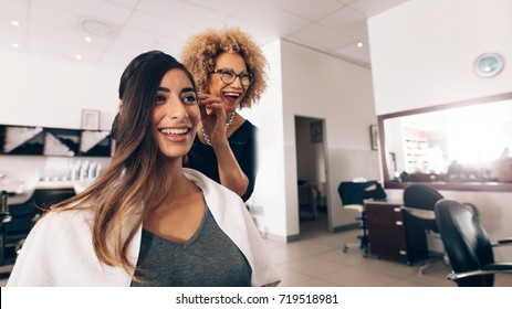 Female hair dresser working on styling a woman 's hair. Hairdresser in a happy mood while working on a woman's hair style.