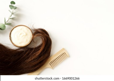 female hair, hair mask and bamboo comb on white background top view, flat lay. copy space. Self care, hair treatment  concept.