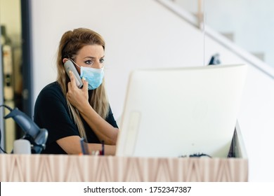 Female hairdresser answering the phone to give her clients an appointment, wearing a protective mask, at a hairdresser's. Business and beauty concepts