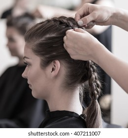 Female hairdresser is braiding young woman's hair