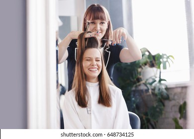 Female hairdresser with comb and scissors makes a haircut for a woman closeup in beauty salon