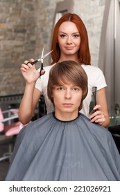 Female hairdresser cutting hair of man client and looking into camera. closeup on handsome man sitting in hair salon and looking into camera