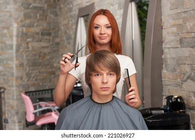 Female hairdresser cutting hair of man client and looking into camera. handsome man sitting in hair salon and looking into camera