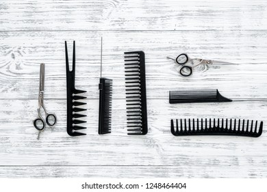 female hairdresser desk with accessories and combs on white wooden background top view