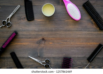 female hairdresser desk with accessories and combs on wooden background top view copyspace