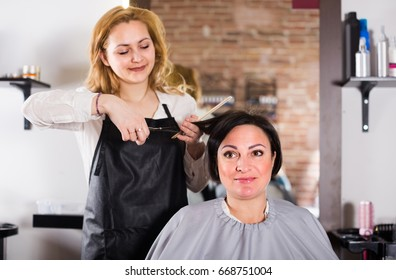 Female hairdresser is doing hairstyle and cut by means of scissors and hairbrush for woman.