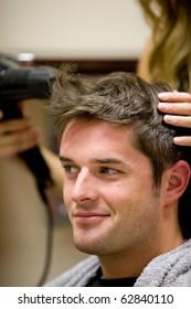 Female hairdresser drying her male customer's hair in her hairdressing salon