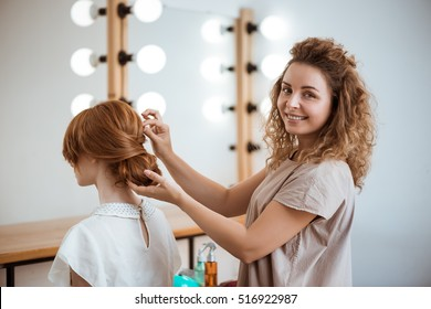 Female hairdresser smiling making hairstyle to redhead girl in beauty salon.