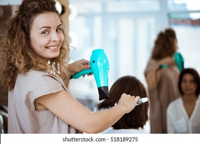 Female hairdresser smiling, making hairstyle to girl in beauty salon.