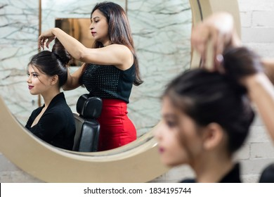 Female hairdresser standing and making hairstyle of a cute lovely young woman in beauty salon, beauty parlour concept.