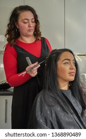 Female hairdressing client sitting while   hairstylist works