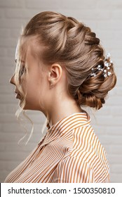 Female hairstyle low bun on blonde hair profile view.