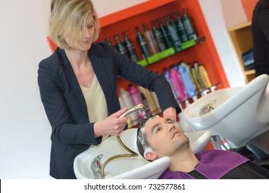 female hairstylist hairdresser washing male customers hair
