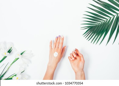 Female hand apply cosmetic cream on white background among flowers, top view