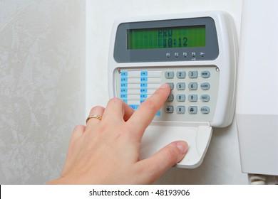female hand arming a burglar alarm system