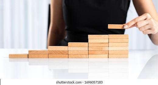 Weibliche Hand, die Holzblockstapel als Treppenstreppe arrangiert. Karriereweg-Konzept für den Geschäftserfolg