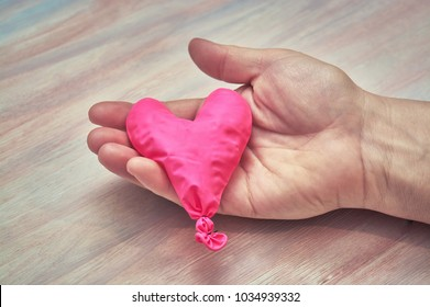 Female hand with a balloon in the shape of a heart. The concept of withered love.