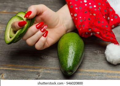 The female hand with beautiful festive New Year's manicure holds the avocado fruit cut by rings