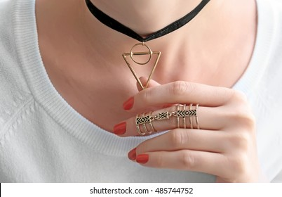 Female hand with beautiful ring holding black choker, close up