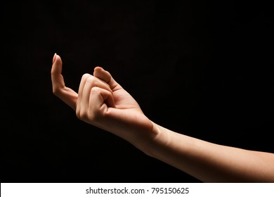 Female hand beckoning with forefinger, isolated on black background. Woman gesturing with one finger, calling up, come here symbol